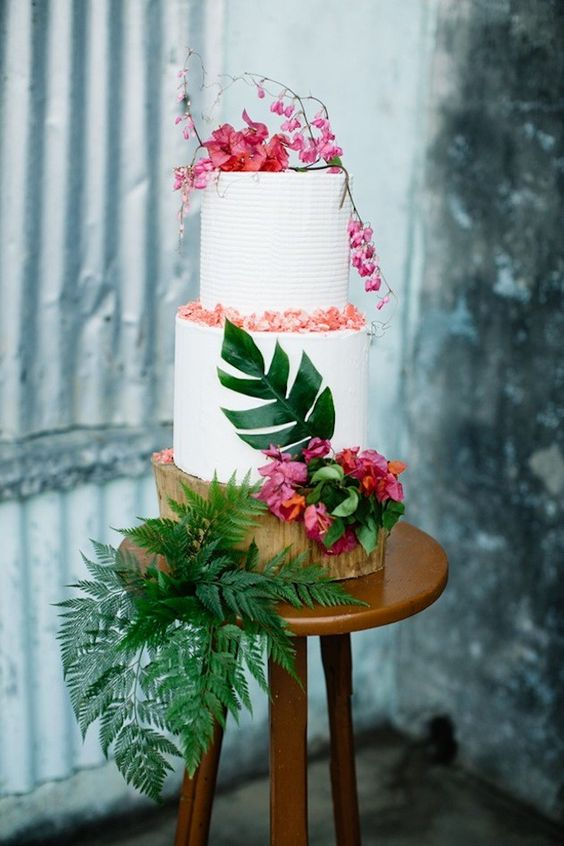a textural white cake with fresh blooms, petals and leaves