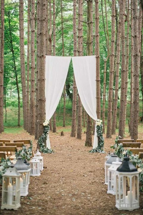 eucalyptus aisle decor and white lanterns, white curtains for the arch
