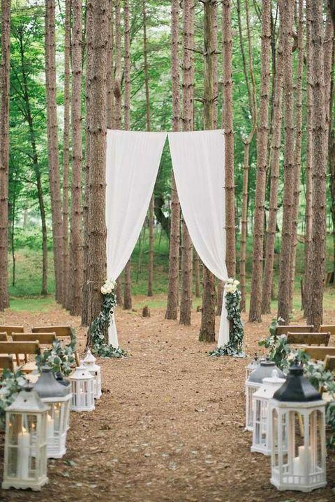 eucalyptus aisle decor and white lanterns, white curtains for the arch