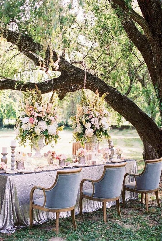 formal garden wedidng reception with a sequin tablecloth and blue chairs