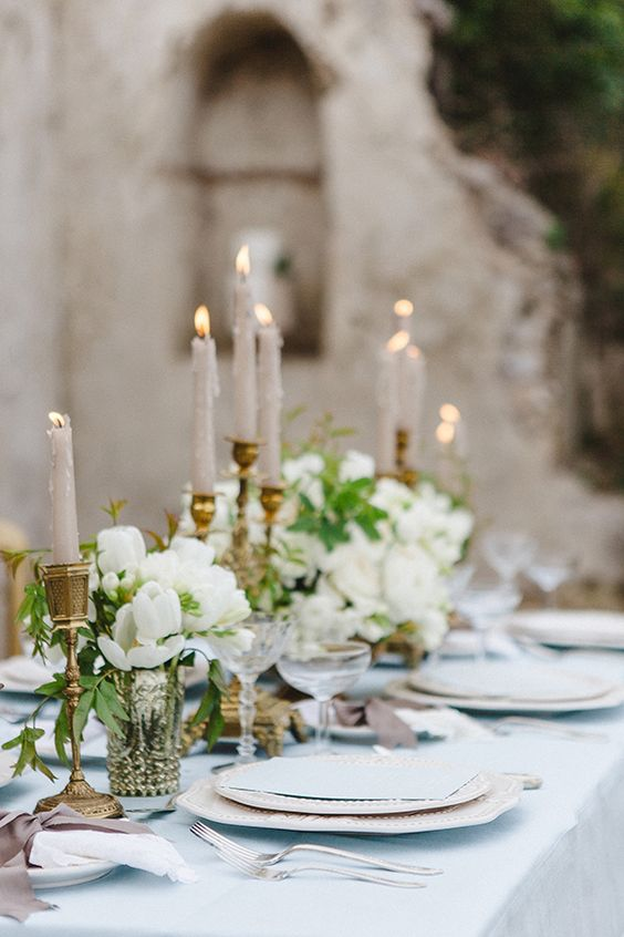 soft blue wedding tablescape with gilded candle holders and ivory flowers