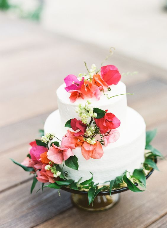a white cake with bold tropical flowers and greenery