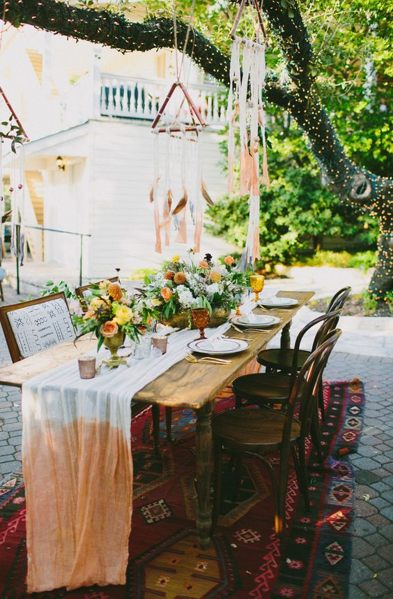 colorful wedding table setting with peachy and yellow flowers and anombre table runner
