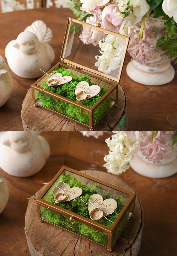 glass wedding box with metal framing, filled with moss and with wooden hearts for attaching rings