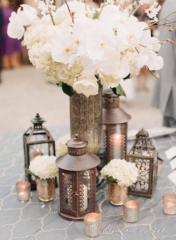 metal lanterns, candle holders and a large vase with white flowers