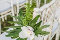 21 tropical-themed outdoor wedding aisle chair decor decorated with white phalaenopsis orchids, palm fronds and ferns
