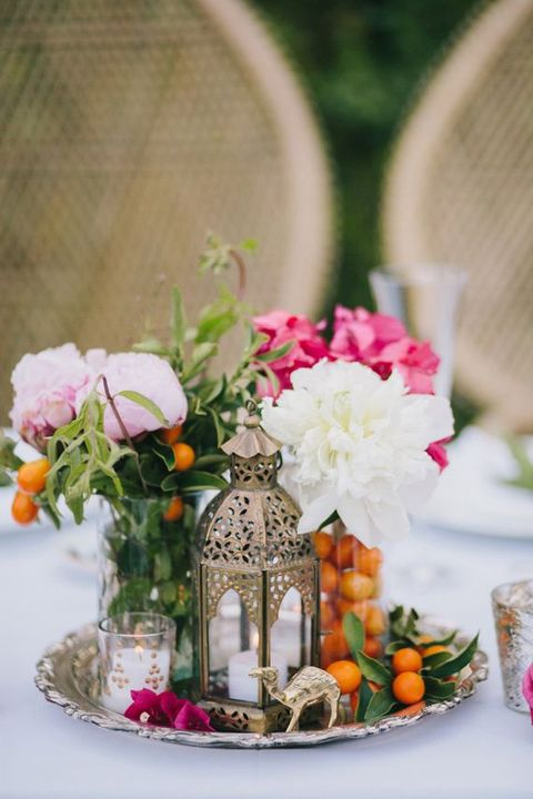 a centerpiece with a lantern, camel, fruits and flowers