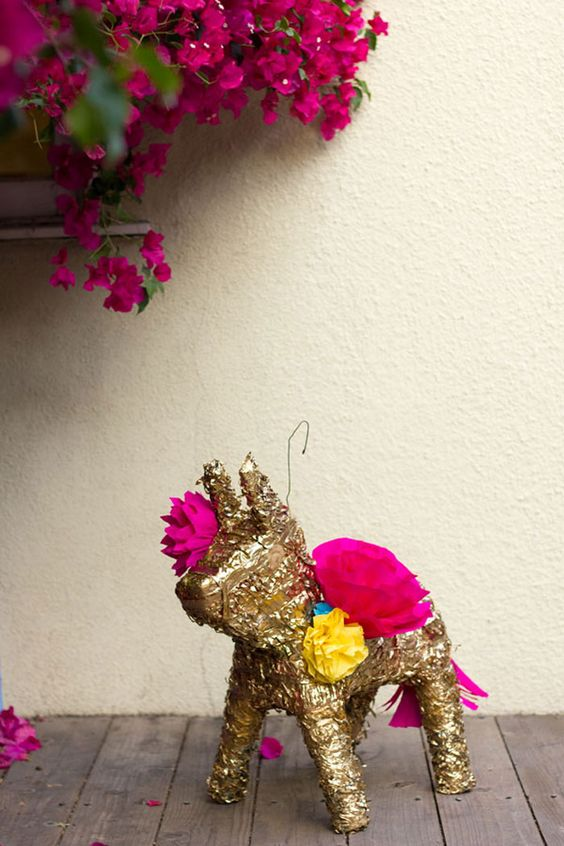 a gold pinata with fuchsia decor for fun