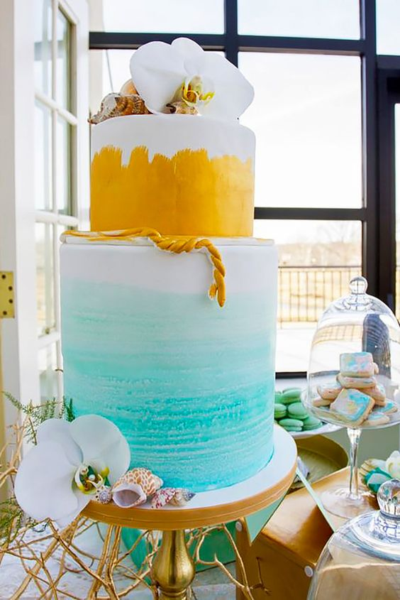 bold watercolor wedding cake in yellow and blue topped with white orchids and shells