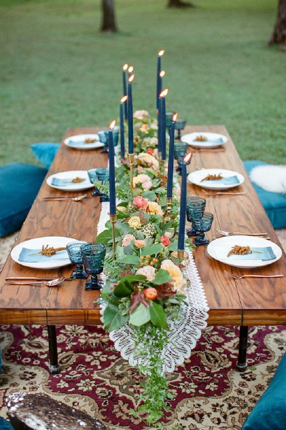 outdoor boho picnic with blues and a lush floral garland