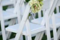 22 tropical aisle marker made of monstera leaf, white hydrangea and lime cymbidium orchids on a white garden chair