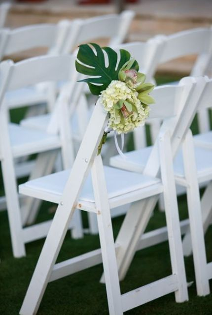 tropical aisle marker made of monstera leaf, white hydrangea and lime cymbidium orchids on a white garden chair