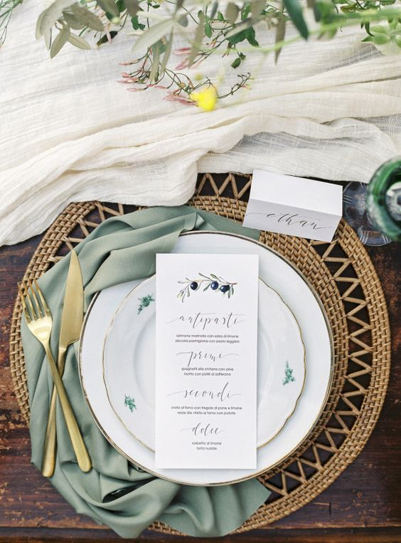 a wicker platter, gold tableware, an olive green napkin