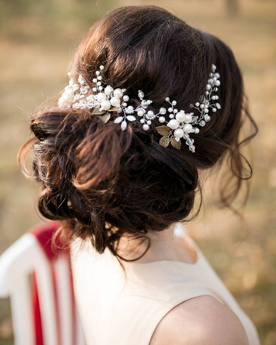 curled wedding updo with a statement vine of sheer and white beads and gold leaves