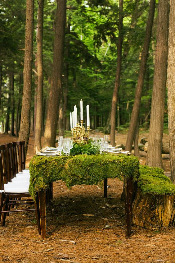outdoor tablescape with a moss tablecloth, candles and greenery, stumps as stools