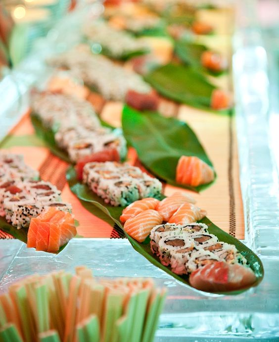 sushi and fish displayed on palm leaves are ideal for a tropical affair