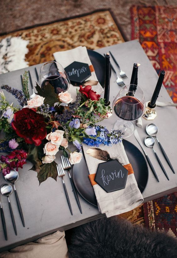 moody summer boho tablescape with bold florals and black candles and plates