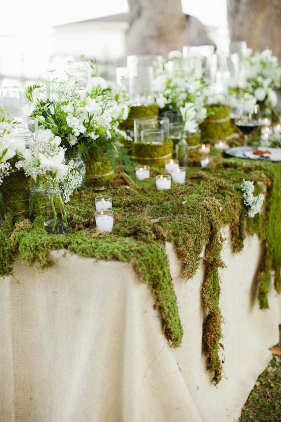 moss table cover, greenery, white blooms and candles