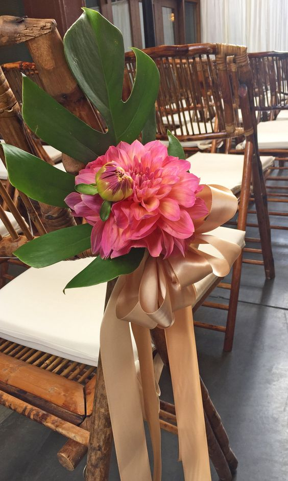 wedding aisle décor with coral dahlias and tropical foliage