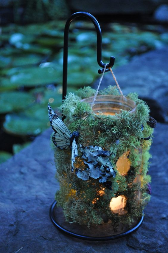 moss lanterns with faux butterflies are great for lining up the aisle