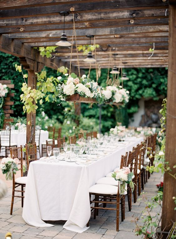 outdoor summer garden reception with white flower decorations over the tables