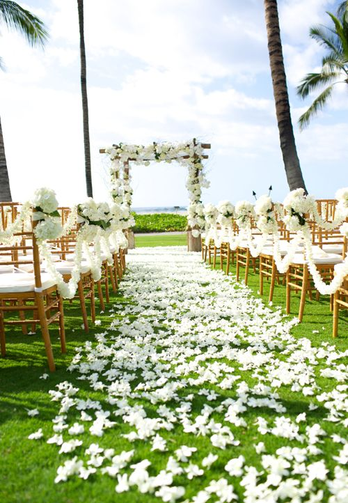 romantic wedding aisle with lush flower garlands, deocr, petals and a white flower wedding arch