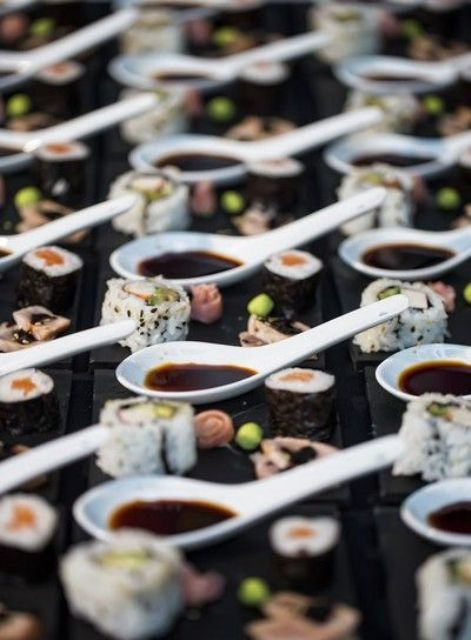 sushi served on small plates with spices and sauce