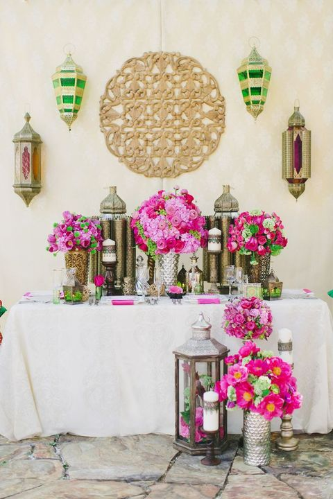 sweetheart table decorated with lanterns, candles and fuchsia colored florals