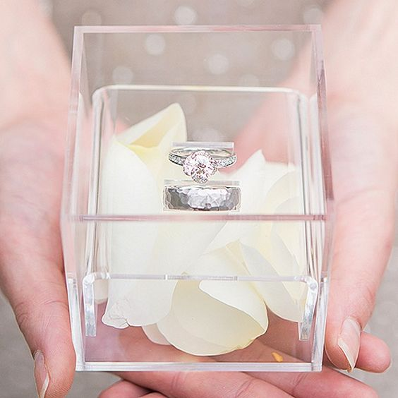 a modern acrylic ring box with white flower petals