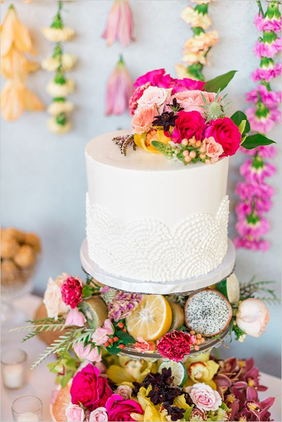 lace wedding cake topped with bold flowers and tropical fruits on display
