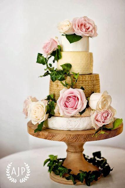 vintage romantic wedding cheese tower on a wooden plate and fresh roses