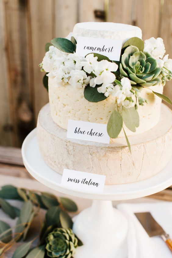 cheese wheel cake with labels, fresh blooms and succulents