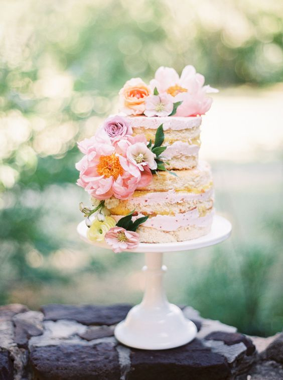 naked wedding cake topped with pink and peachy flowers