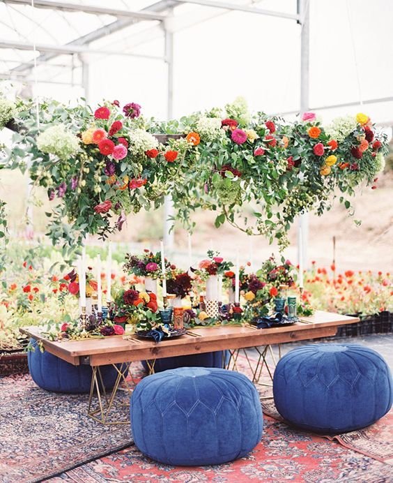 oversized floral hanging over the table and blue Moroccan poufs
