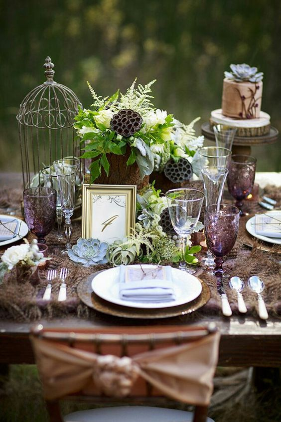 woodland table setting with a feather table runner, greenery, lotus, wood slices and succulents