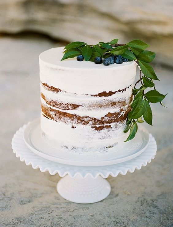 minimalist naked wedding cake topped with blueberries and leaves