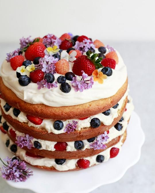 naked wedding cake with flowers and ripe summer berries