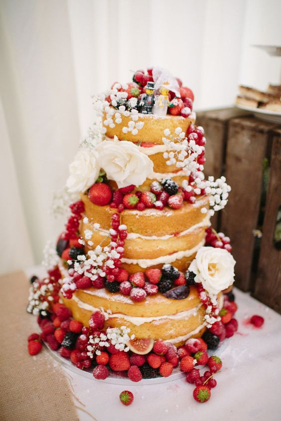 naked wedding cake with fresh berries and baby's breath