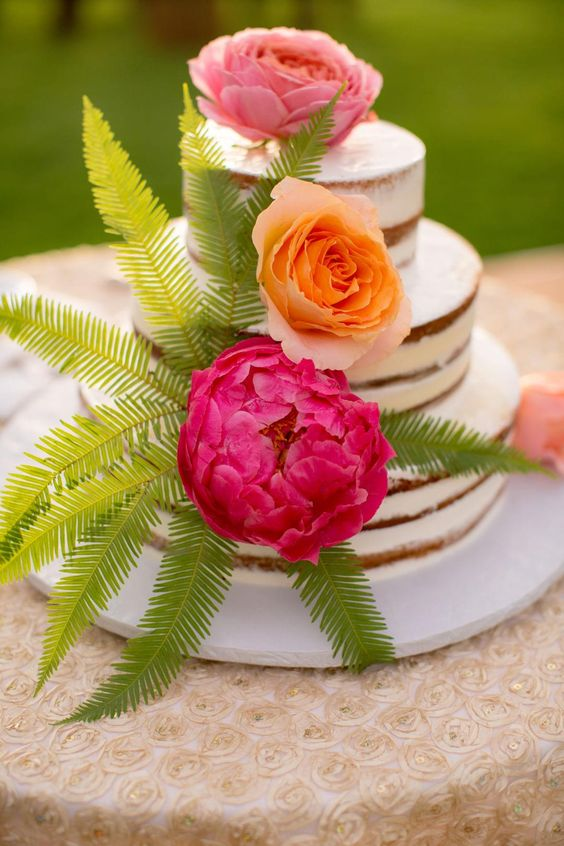 naked wedding cake with fresh blooms and leaves