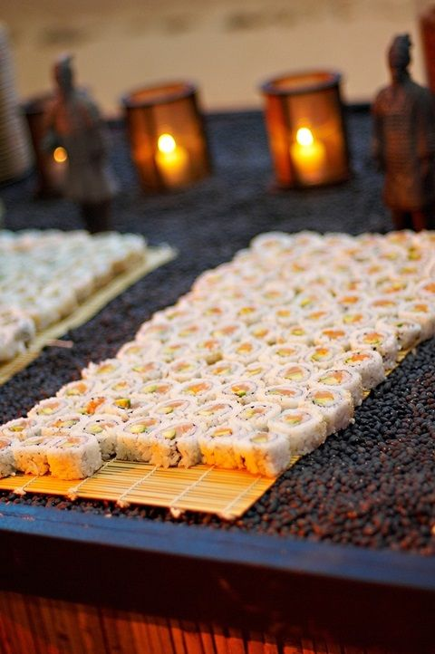 white rice covered sushi look spectacular on a surface covered with black beans