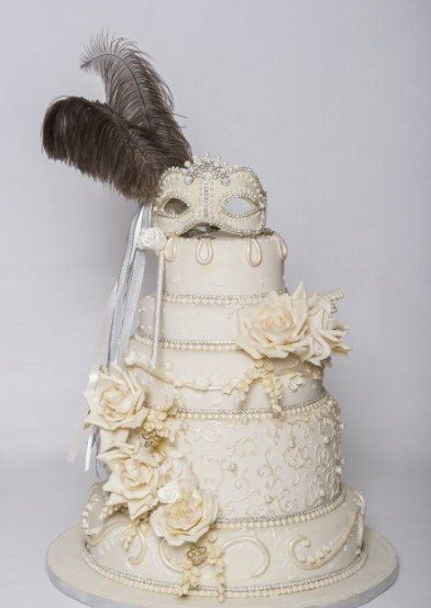 a lush ivory wedding cake with sugar roses and a mask