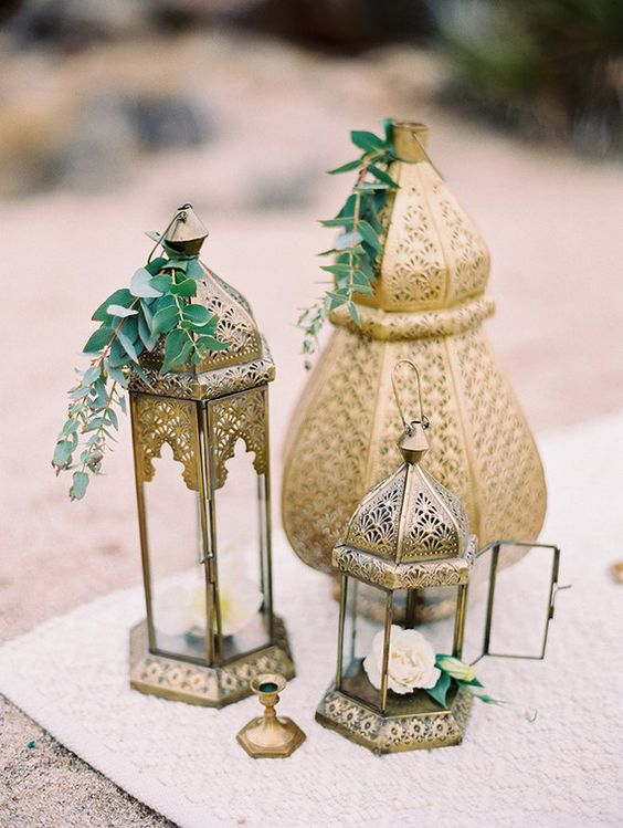 an arrangement of Moroccan lanterns with greenery and flowers