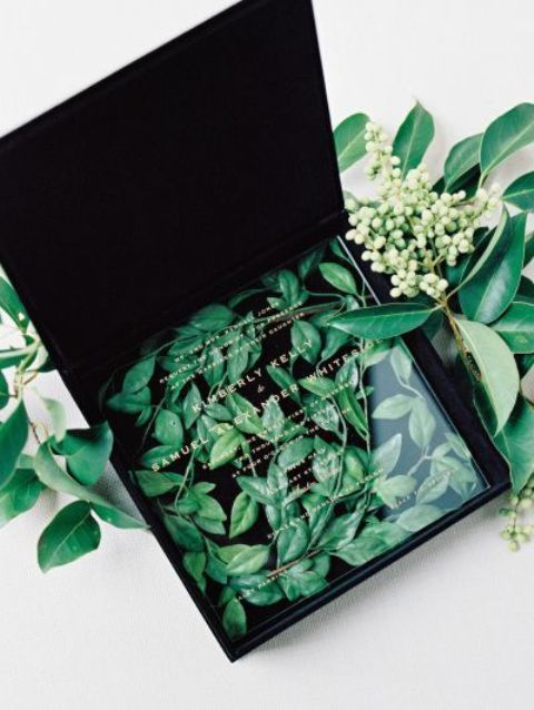 clear acrylic wedding invites in a black velvet box with leaves inside
