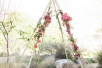 32 teepee-style wedding chuppah with antlers and bold flowers