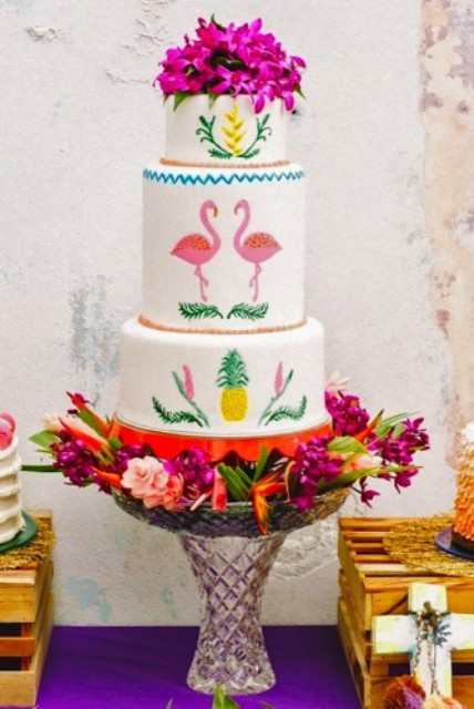 wedding cake topped with flowers and with flamingos and pineapple decor