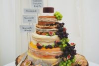 33 a rustic display with grapes, figs, straw and toppers on an oversized wooden slice
