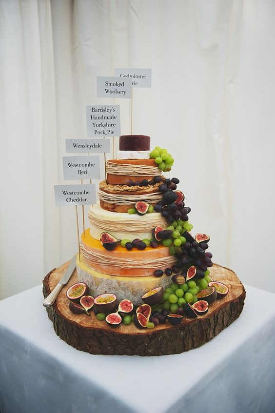 a rustic display with grapes, figs, straw and toppers on an oversized wooden slice