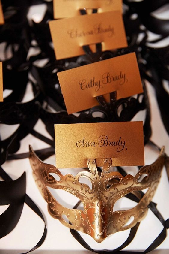 gold masks for women and black masks for men in lieu of escort cards