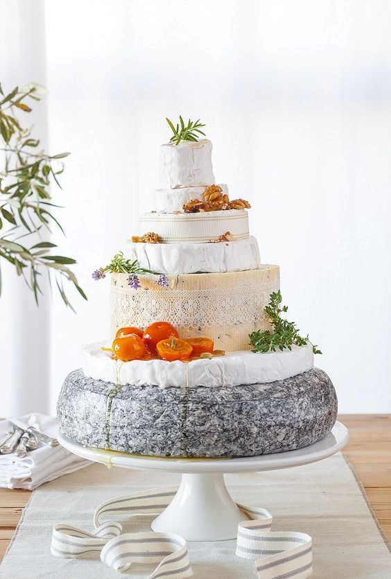 a rustic cheese tower on a stand, tomatoes, herbs, nuts and herbs