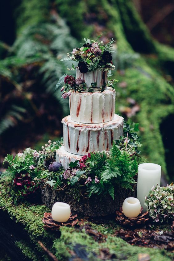 whimsy wedding cake with greenery, dark flowers and uneven frosting